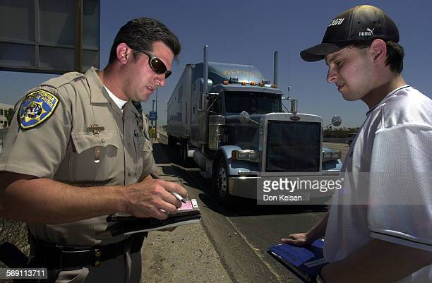 California Highway Patrol Officer Scott Moorhouse writes this trucker a citation for exceeding the speed limit on the North I–5 just South of...