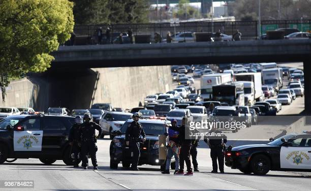 California Highway Patrol officers confront a Black Lives Matter protester as he marches Interstate 5 during a demonstration on March 22 2018 in...