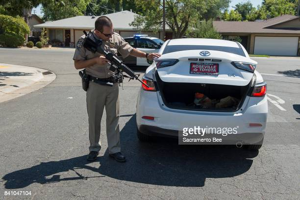 California Highway Patrol officers look for suspects in the trunk of a car after two CHP officers were shot and a Sacramento County Sheriff's...