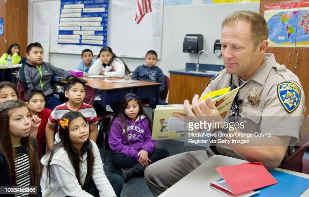 California Highway Patrolman Kevin Johnson reads Dr Seuss's Fox in Socks to a fourthgrade class at Heroes Elementary School He was volunteering...