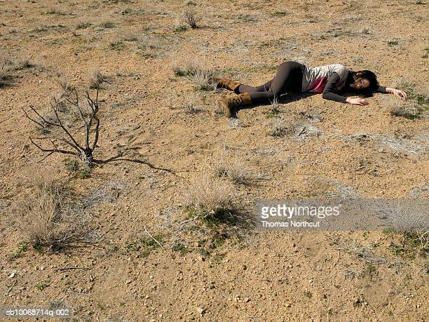 USA, California, Idyllwild, Woman lying on ground in desert