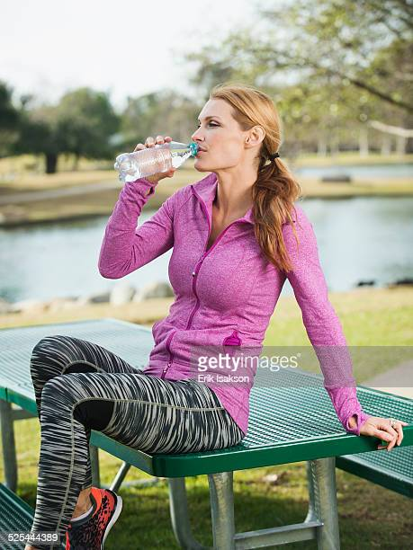 USA, California, Irvine, Woman in park drinking water