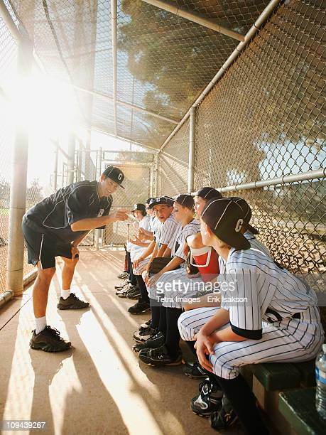 USA, California, Ladera Ranch, Boys (10-11) from little league sitting on dugout while coach talking
