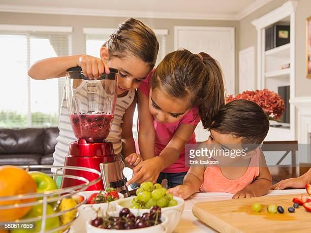 USA, California, Ladera Ranch, Children (2-3, 6-7, 8-9) preparing fruit cocktails