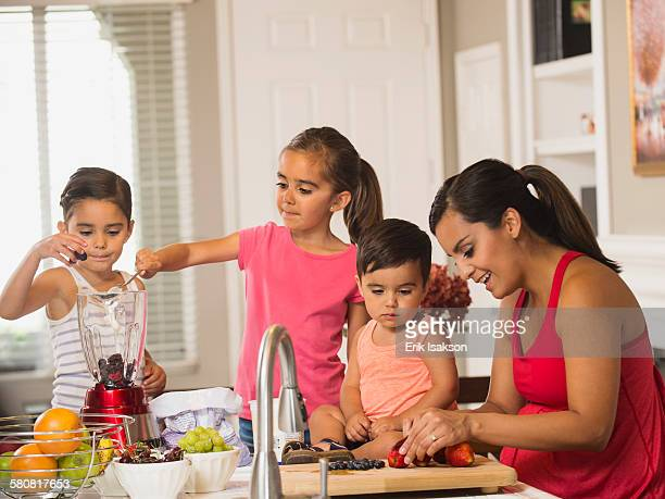 USA, California, Ladera Ranch, Mother and children (2-3, 6-7, 8-9) preparing fruit cocktails