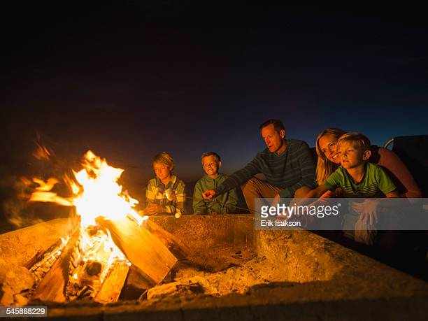usa, california, laguna beach, family with three children (6-7, 10-11, 14-15) cooking marshmallows - campfire stock pictures, royalty-free photos & images