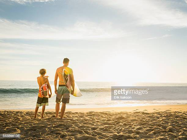 USA, California, Laguna Beach, Father and son (14-15) looking at sea