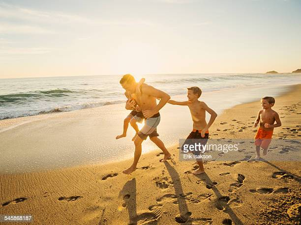 usa, california, laguna beach, father playing football on beach with his three sons (6-7, 10-11, 14-15) - zwembroek stockfoto's en -beelden