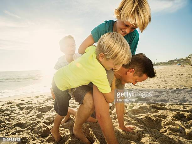 USA, California, Laguna Beach, Father playing with his sons (6-7, 10-11, 14-15) on beach