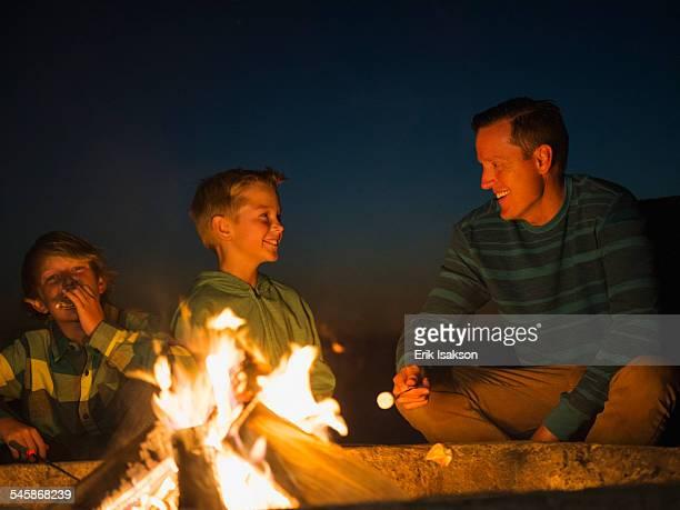 USA, California, Laguna Beach, Man talking with his sons (10-11, 14-15) by campfire