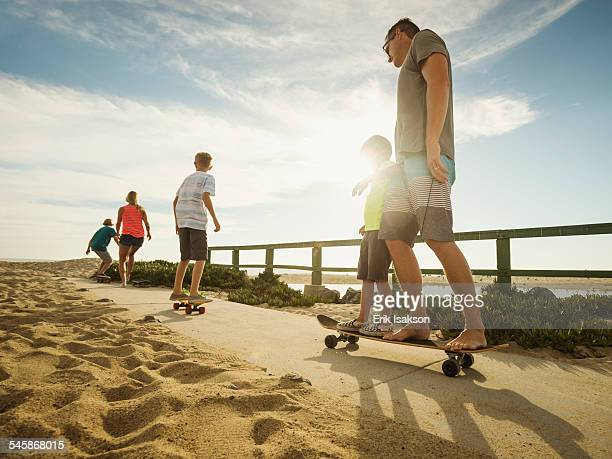 USA, California, Laguna Beach, Parents skateboarding with their children (6-7, 10-11, 14-15)