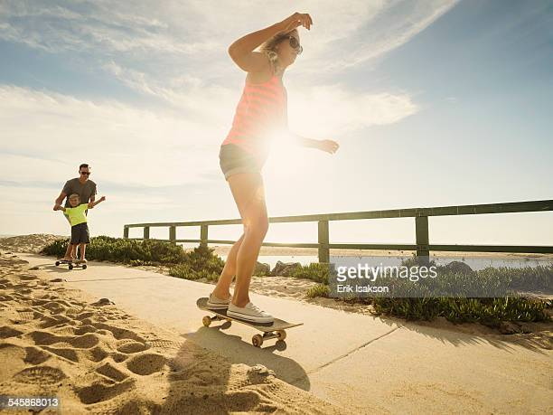 usa, california, laguna beach, parents skateboarding with their son (6-7) - orange county california stock pictures, royalty-free photos & images