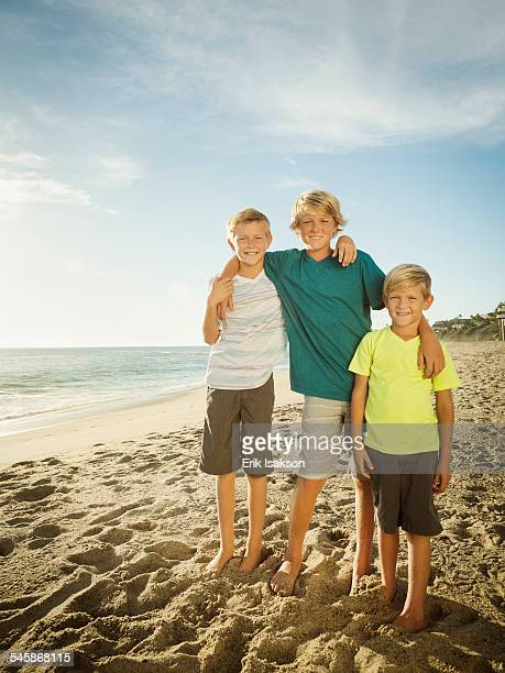USA, California, Laguna Beach, Portrait of brothers (6-7, 10-11, 14-15) on beach