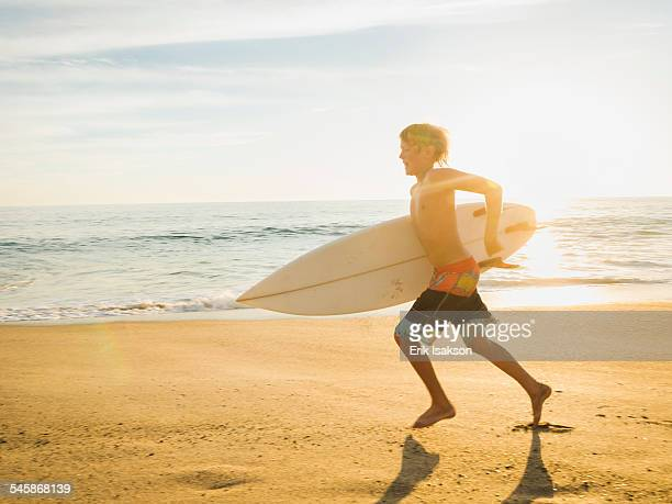 USA, California, Laguna Beach, Teenage boy (14-15) with surfboard running on beach