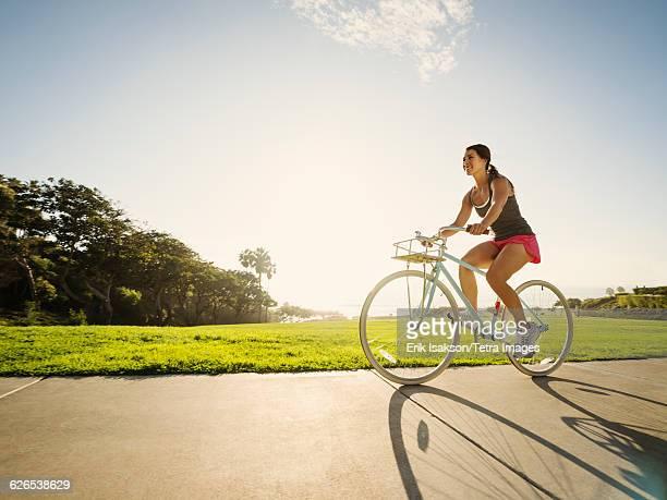 USA, California, Laguna Beach, Young woman cycling in park