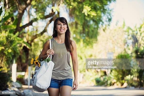 USA, California, Laguna Beach, Young woman with shopping bag walking