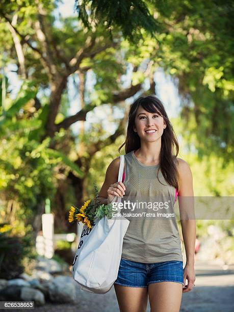 USA, California, Laguna Beach, Young woman with shopping bag walking