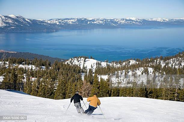 USA, California, Lake Tahoe, two men downhill skiing, rear view