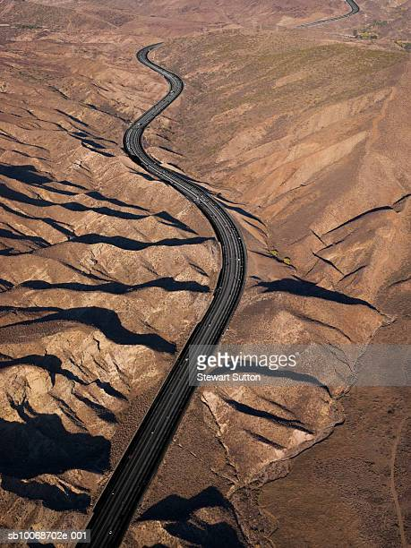 USA, California, Lancaster, Winding road passing through mountains, aerial view