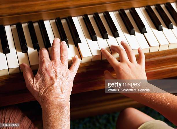 USA, California, Lawndale, Grandmother and granddaughter hands on piano