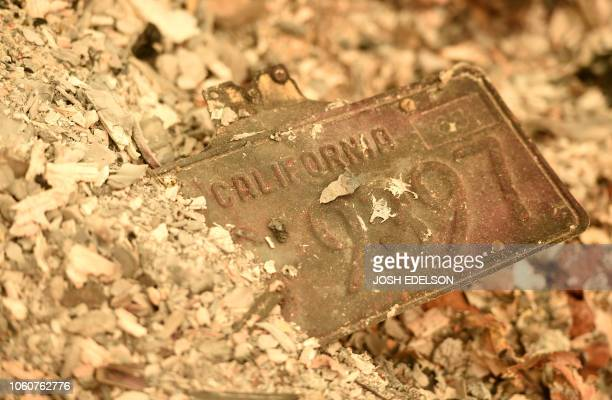 A California license plate is seen partially buried in a pile of ash at a burned residence after the Camp fire tore through the region in Paradise...