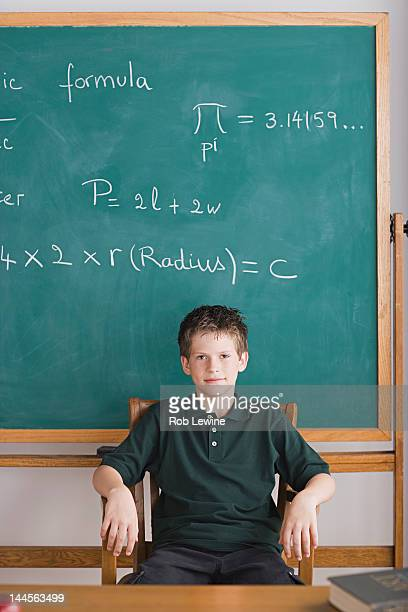 usa, california, los angeles, boy sitting in teachers chair, blackboard in background - child prodigy stock pictures, royalty-free photos & images