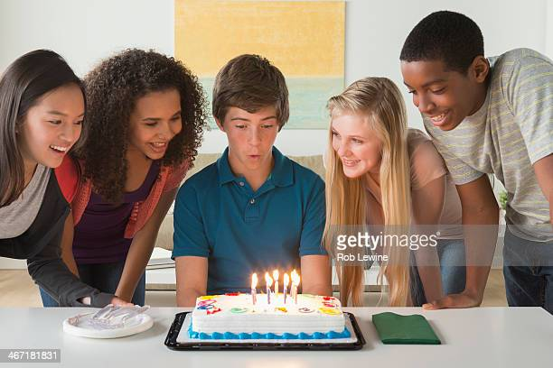 USA, California, Los Angeles, Children (12-13,14-15,16-17) blowing candles on birthday cake