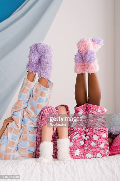 USA, California, Los Angeles, Close op of legs of three girls (10-11) lying on bed with feet up