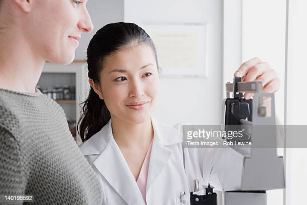 USA, California, Los Angeles, Close up of female doctor measuring woman's weight