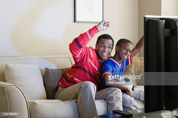 USA, California, Los Angeles, Father and Son (12-13) watching sports on tv