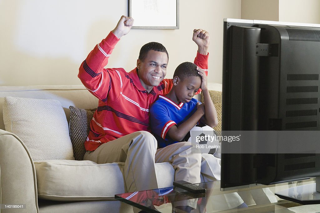 USA, California, Los Angeles, Father and Son (12-13) watching sports on tv : Stock Photo
