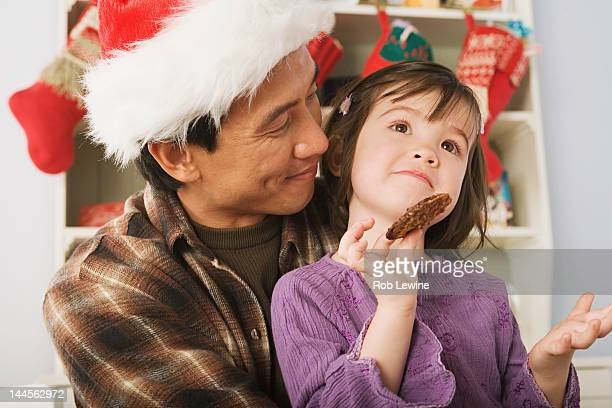 USA, California, Los Angeles, Girl and father wearing santa hat