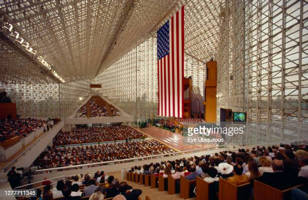 California, Los Angeles, Interior view of Crystal Cathedral on Memorial Day with people sittting in stands surrounding the American flag.