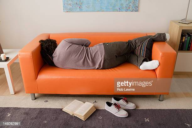 usa, california, los angeles, man sleeping on sofa - laziness stock pictures, royalty-free photos & images