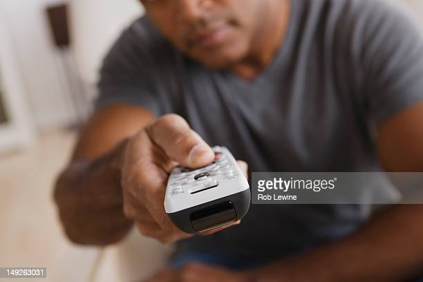 USA, California, Los Angeles, Mature man holding remote control, focus on foreground
