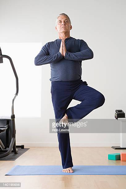 usa, california, los angeles, mature man practicing yoga on mat - standing on one leg stock pictures, royalty-free photos & images
