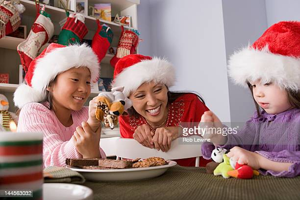 USA, California, Los Angeles, Mother with two daughters playing at Christmas morning