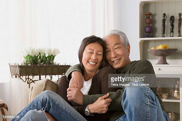 usa, california, los angeles, older couple in warm embrace - asian 50 to 55 years old woman stock photos and pictures