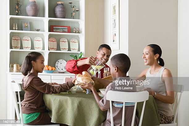usa, california, los angeles, parents and children (10-13) eating dinner together - african american family dinner stock photos and pictures