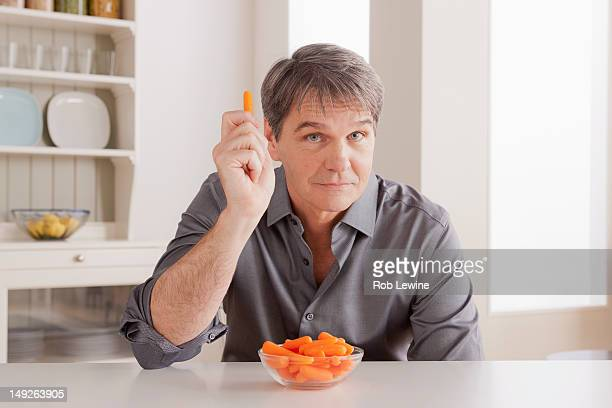 USA, California, Los Angeles, Portrait of mature man with baby carrot on table