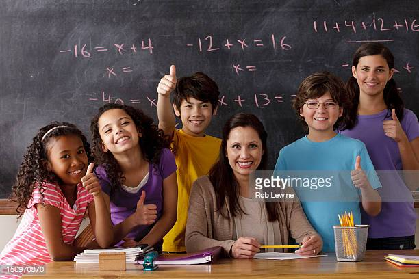 USA, California, Los Angeles, portrait of pupils (10-11, 12-13) and teacher with blackboard in background