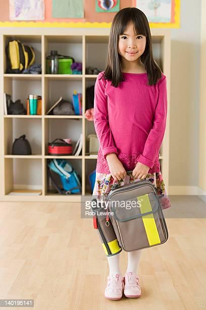 USA, California, Los Angeles, Portrait of schoolgirl (6-7) holding backpack