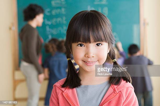 USA, California, Los Angeles, Portrait of smiling girl (6-7) with classmates in background