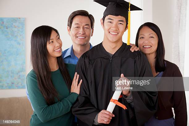 USA, California, Los Angeles, Portrait of young man in graduation gown with family