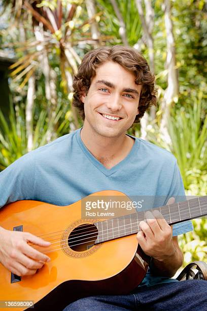 USA, California, Los Angeles, Portrait of young man playing guitar