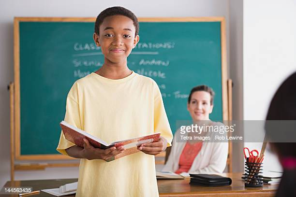 USA, California, Los Angeles, Schoolboy posing with book, teacher in background