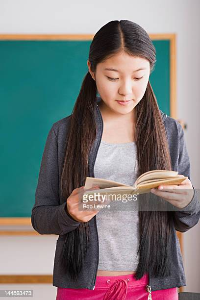 USA, California, Los Angeles, Schoolgirl reading book in front of blackboard