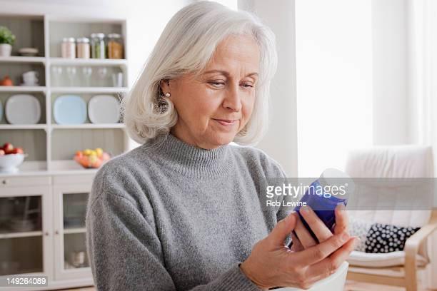 USA, California, Los Angeles, Senior women reading label on medicine bottle