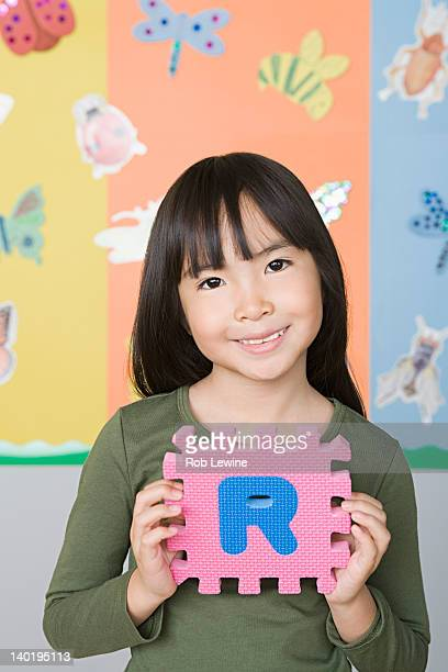 USA, California, Los Angeles, Smiling girl (6-7) holding letter R