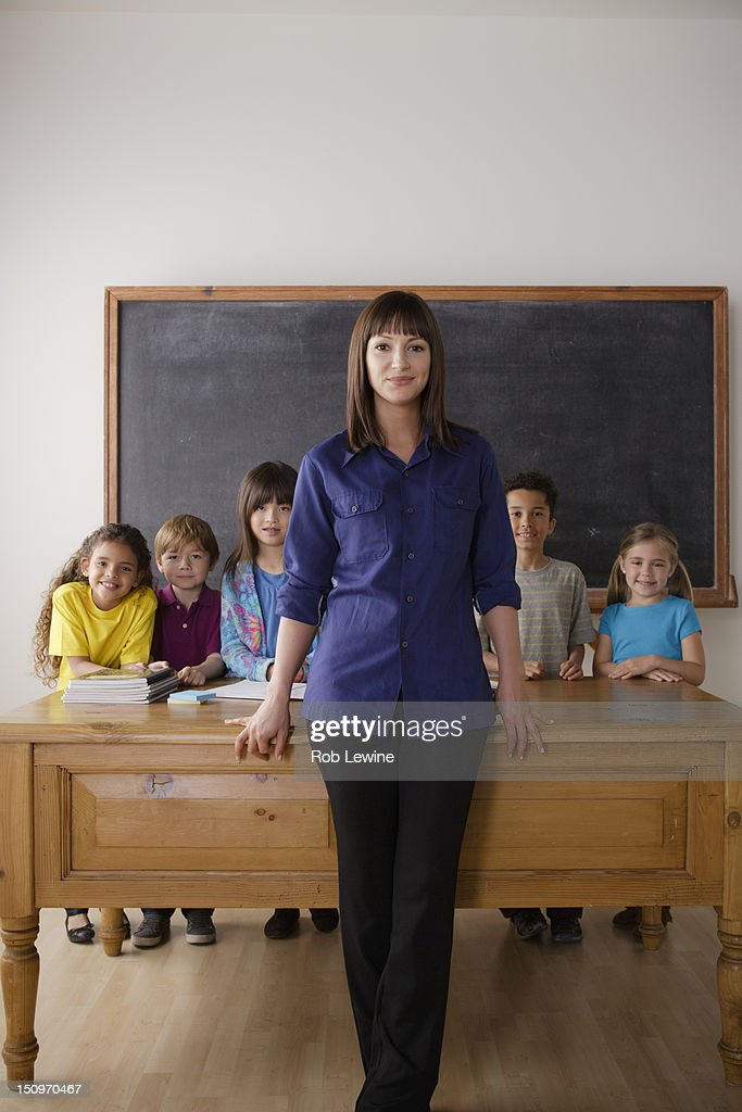 Usa California Los Angeles Teacher Standing By Desk With Group Of